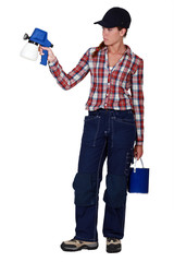 A female painter with a spray gun.