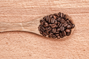 spoon with  coffee beans  on a wooden table