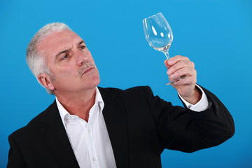 Man examining a wine glass