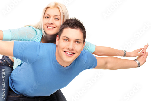 Young happy couple posing piggyback