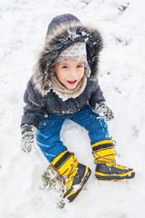 Little boy having fun on winter day