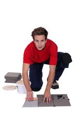 Man tiling the floor