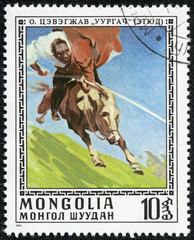 stamp printed in Mongolia showing man riding a horse