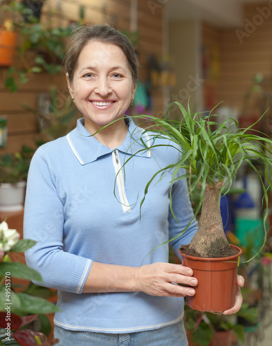 Happy mature woman with Nolina in pot