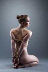 Pretty young woman with shibari sitting on floor
