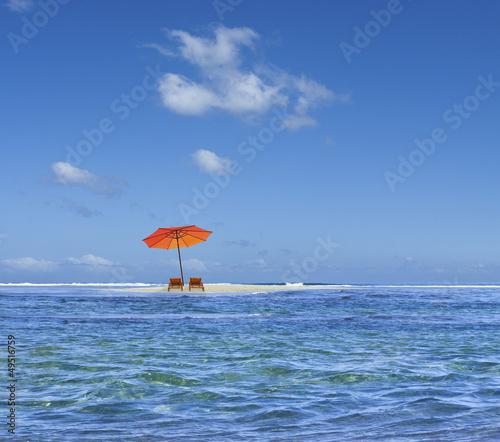parasol sur îlot de sable blanc