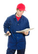 Young male plumber in uniform with wrench reading manual.