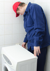 Young worker repairing washing machine