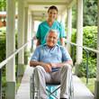 Krankenschwester schiebt Senior im Rollstuhl