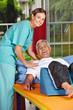 Mann bei Krankengymnastik neben Physiotherapeutin