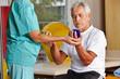 Senior mit Igelball bei Physiotherapie