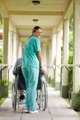 Krankenpflegerin schiebt Mann im Rollstuhl