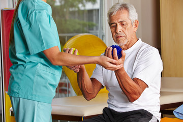 Senior mit Igelball bei Physiotherapie