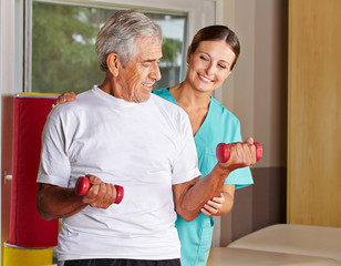 Senior hebt Hanteln bei Physiotherapie