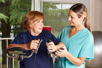 Krankenschwester neben Seniorin bei Physiotherapie