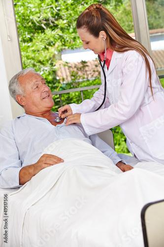 Ärztin mit Stethoskop bei einem Senioren