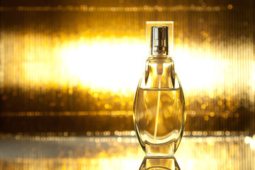 Bottle of perfume on gold background
