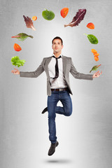 Young businessman jumping with vegetables in the air