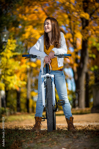 Girl biking in autumn park
