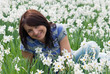 Smiling woman sitting among daffodils
