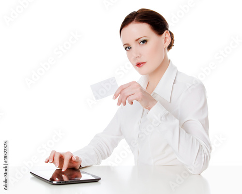 Woman sitting with a tablet computer and holding a credit card