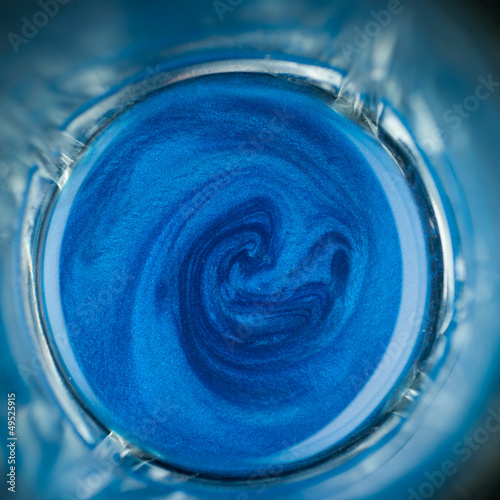 blue pigment mixed with oil in a glass, macro
