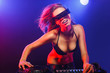 Excited DJ girl wearing glasses on decks on the party