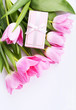Pink tulips and gift box on a white background