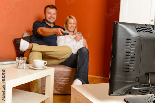 Happy couple watching tv evening changing channels