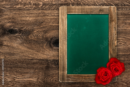 blank green blackboard with red roses