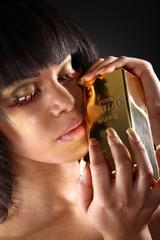 Hübsche Frau mit Goldbarren