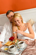 Happy lovers lying bed eating romantic breakfast