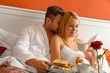 Snuggling couple romantic morning bed drinking coffee