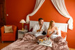 Loving couple drinking coffee hotel bedroom