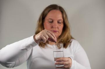 Frau nimmt Medikamente ein