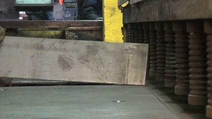 Metal worker puts a plate under pressure
