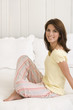 Smiling Pretty Woman Sitting On A Bed Wearing Pajamas