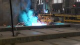 blue sparks fly from welding, people work