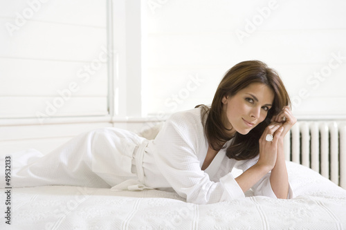 Beautiful Woman In A White Dressing Gown Lying On Her Bed