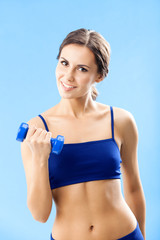 Woman in fitness wear with dumbbell, over blue