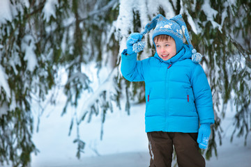Portrait of a little boy playing in winter forest