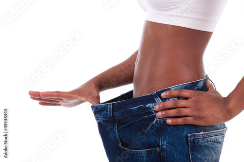 Young african woman in old jeans pant after losing weight