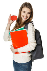 Woman with backpack holding noteebooks showing credit card