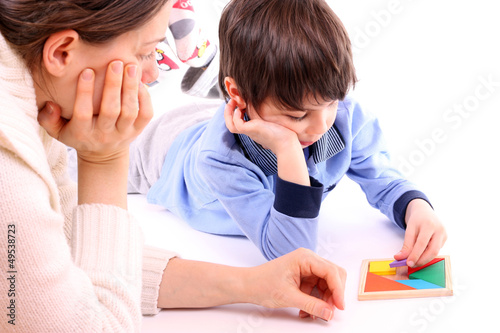 Cute kid and mother playing with tangram