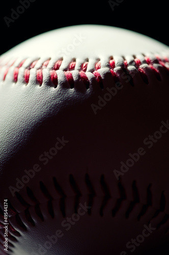 Vertical shot of a baseball ball over black background, macro
