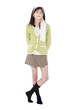 Unsmiling confident young girl in green sweater standing, isolat