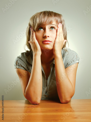 A young frightened woman sitting at the desk