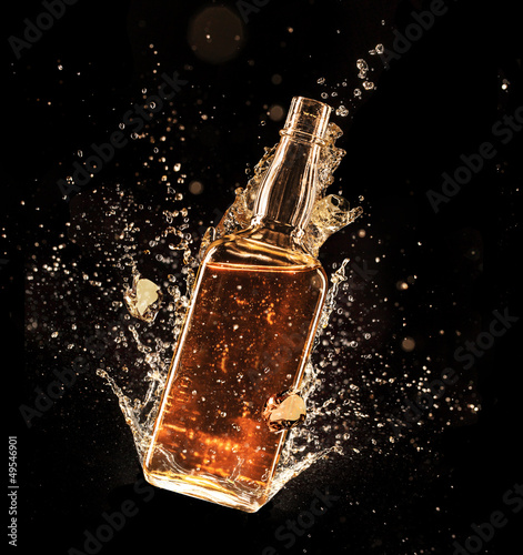 Papiers peints Bar Concept of liquor splashing around bottle on black background