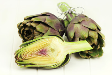 Fresh purple artichoke bundle on white wooden backround