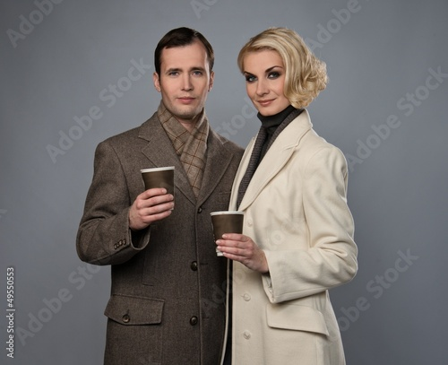 Elegant couple with cups isolated on grey